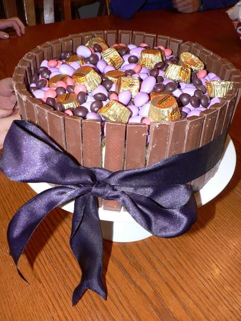 A candy cake made of Kit Kat exterior filled with Reeses peanut butter cups and M&Ms on a round white plate with a dark purple ribbon