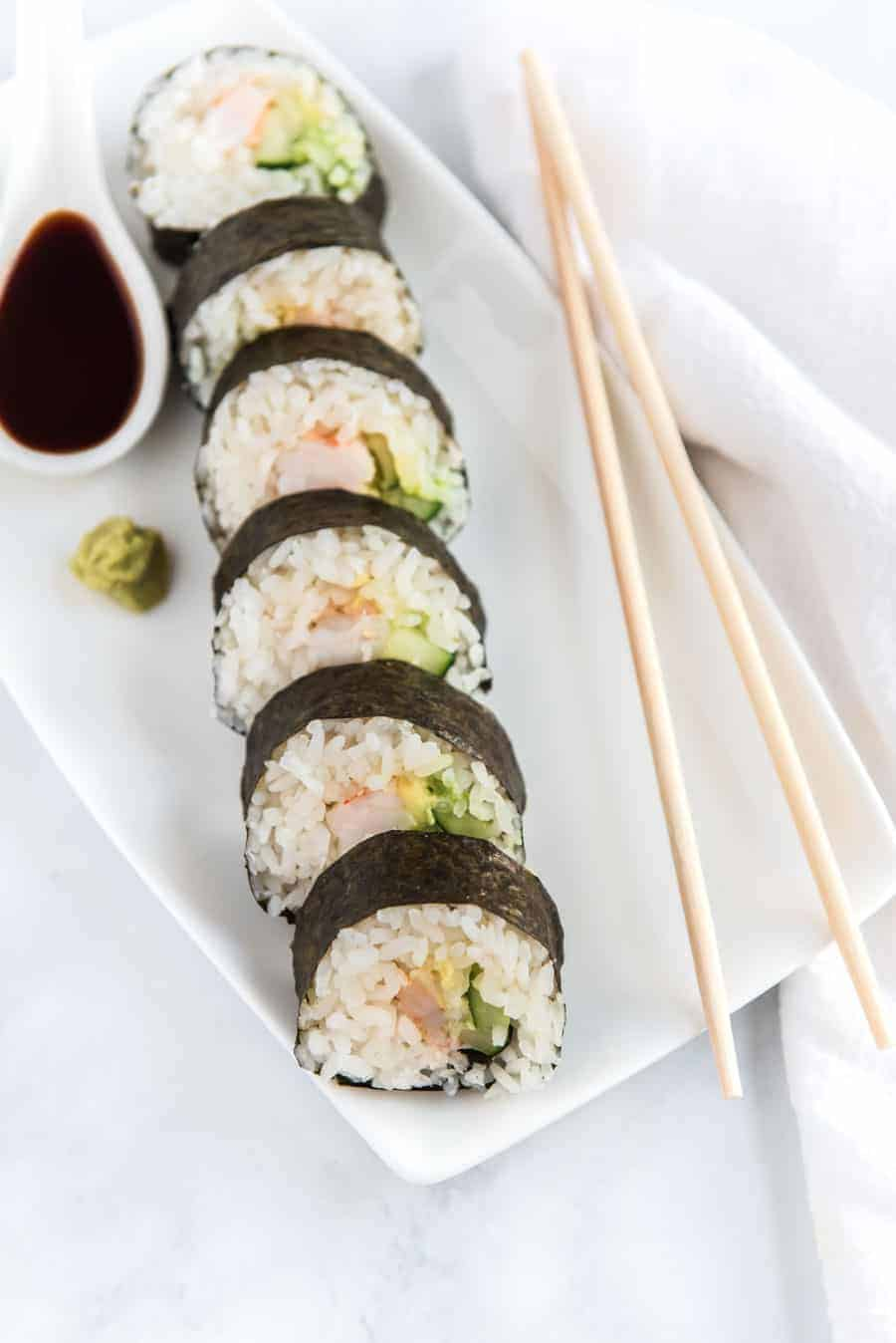 easy shrimp sushi roll on white dish with soy sauce and chopsticks