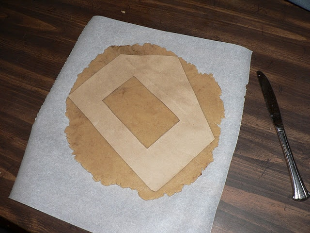 Gingerbread dough rolled out on parchment paper with a house-shaped parchment stencil on top