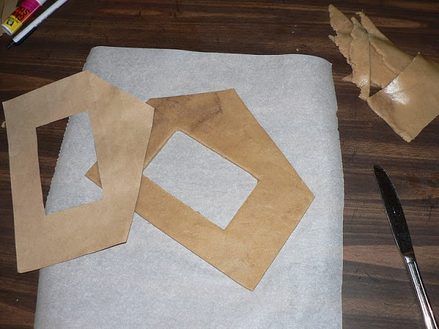 Gingerbread dough in the shape of a house on a sheet of parchment paper