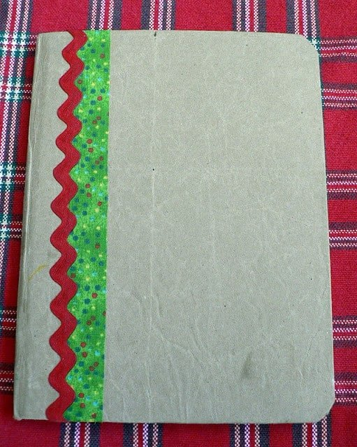 A homemade journal with a tan cover and two christmas-colored ribbons on the left side