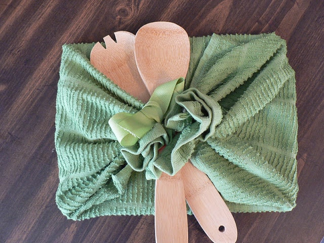 A square gift wrapped in a green tea towel with two wooden spoons