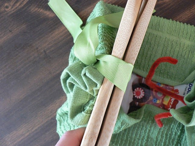 Image of the process of wrapping a gift in a green tea towel with green ribbon and wooden spoons