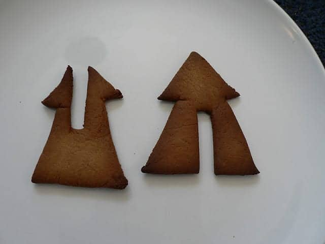 Baked gingerbread pieces in the shape of trees with notches to fit together