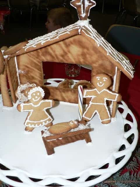 A homemade gingerbread manger with two gingerbread people and a gingerbread baby in a manger