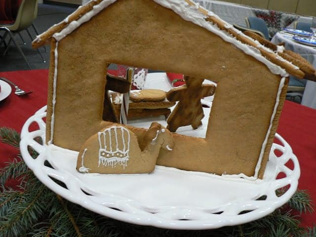 A gingerbread camel looking through the back of a gingerbread stable