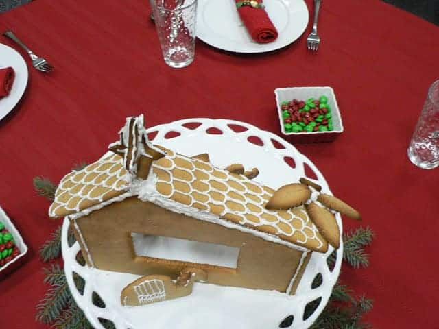 A Christmas-themed table setting with red tablecloth, red and green candies in a dish, and a gingerbread manger scene in the center