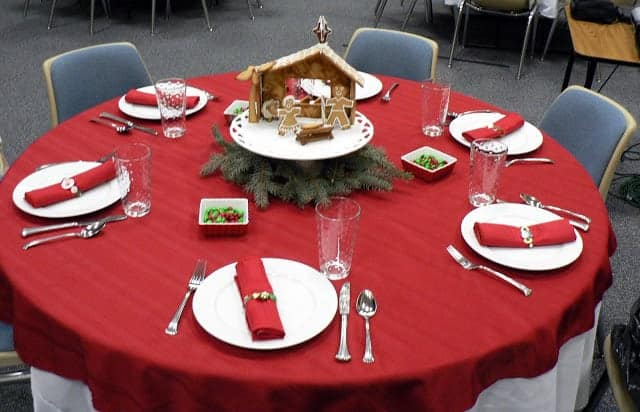 A Christmas-themed table setting on a round table with a homemade gingerbread manger scene centerpiece