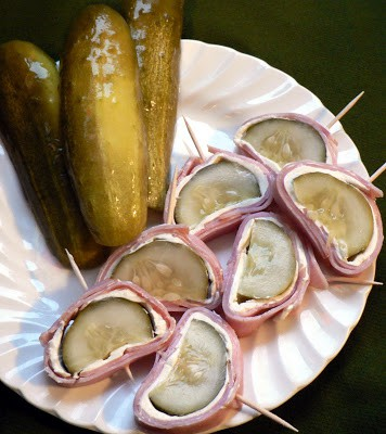 A white plate with three whole pickeles and pickle slices wrapped in cream cheese and ham on toothpicks