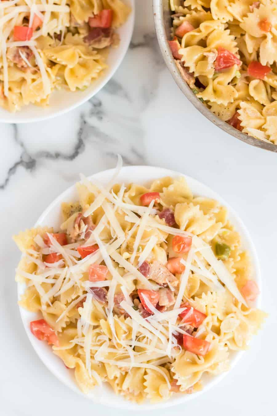 Bowtie pasta in a bowl with chunks of tomato, a light cream sauce, and shredded Parmesan cheese on top.