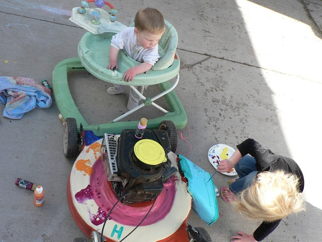 Top view of a paint-decorated lawnmower next to a baby in a walker and a little girl with paints