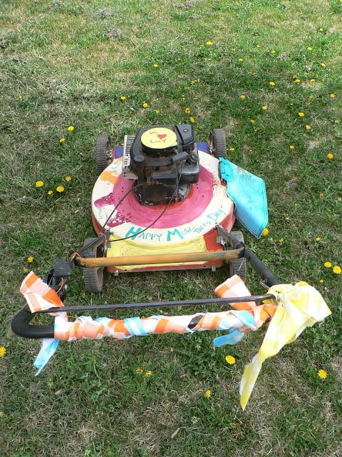 A push lawnmower decorated with paint, hand prints, ribbons, and the words Happy Mow-thers Day