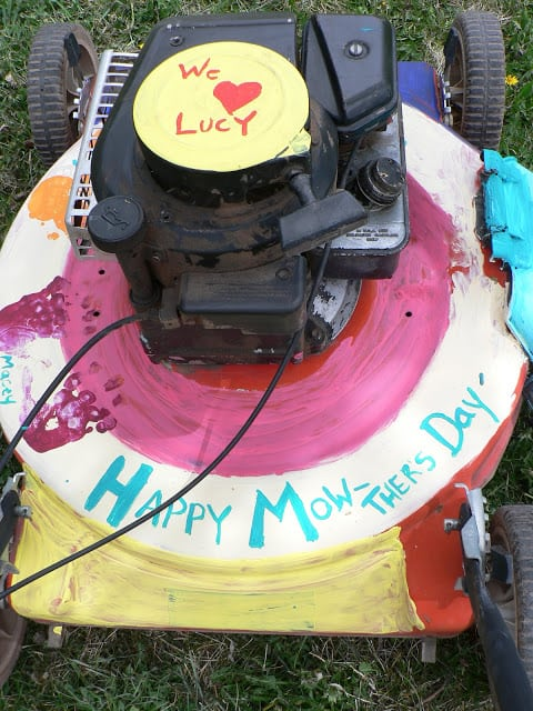 Close-up view of a hand-painted push lawnmower with the words We love Lucy and Happy Mow-thers Day