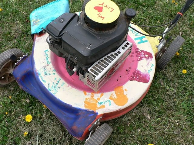 Top view of a painted push lawnmower with children's handprints