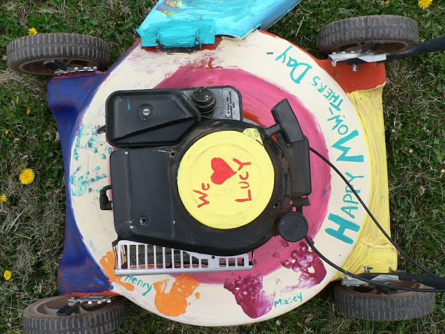 Top view of a paint-decorated push lawnmower with the words We Love Lucy and Happy Mow-thers Day
