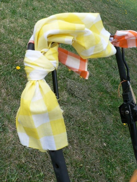 Yellow and orange checked fabric tied around the handle of a push lawnmower