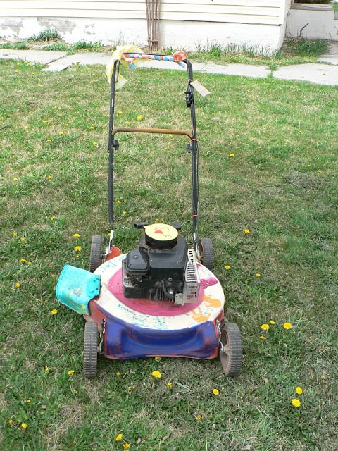 Front view of a paint-decorated push lawnmower with children's handprints