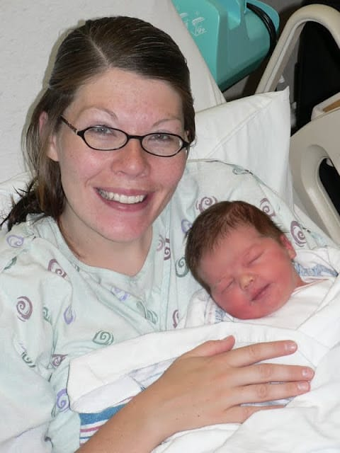A woman in a hospital bed smiling and holding a newborn baby