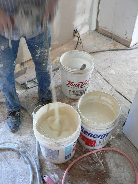 A contractor mixing white sheetrock mud in buckets