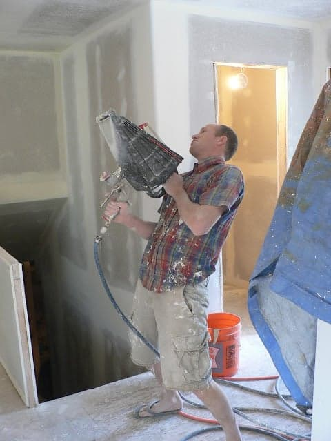 A man holding a triangular-shaped tool with a hose to add wall texture