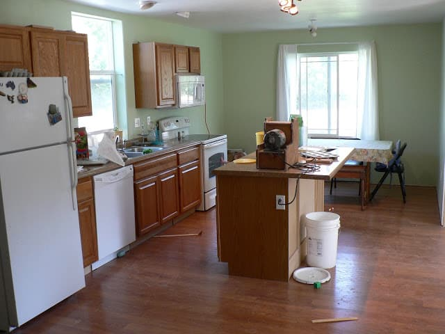 A photo of a simple kitchen with green walls, wooden cabinets and an island in the middle