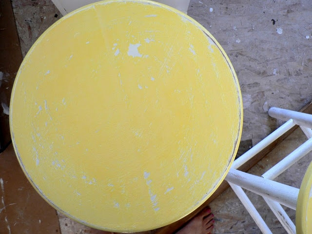 Top view of a yellow distressed-painted bar stool with white legs