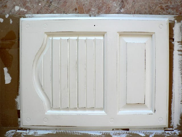 A white distressed-painted cabinet door