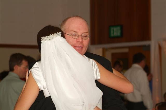Back view of a bride with a veil hugging her father