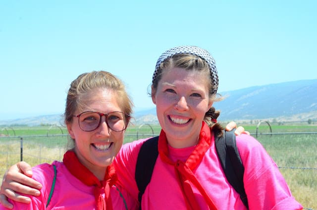 Image of two women outdoors, smiling with an arm around each other and both wearing magenta tops