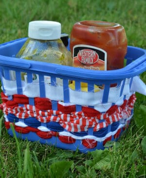 A blue plastic basket for condiments decorated with red, white and blue ribbons