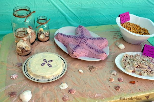 A party table with sand and shell decorations, a sand dollar cake, and a starfish cake