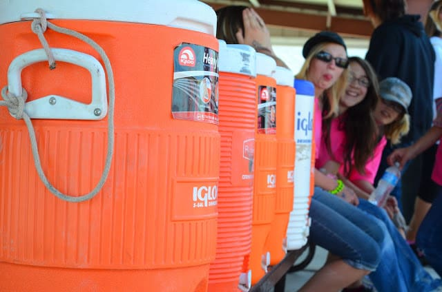 A few women sitting on a bench next to several orange beverage coolers