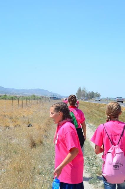 A group of girls in pink shirts looking into a fenced area in a prairie field
