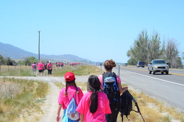 An adult woman walking with two girls wearing pink shirts and backpacks on a dirt path along a prairie field