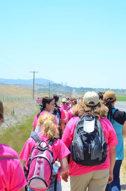 A group of women and girls in pink shirts walking along a prairie field