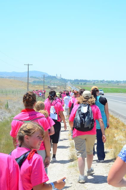 A group of women and children in pink shirts walking along a dirt path near a prairie field