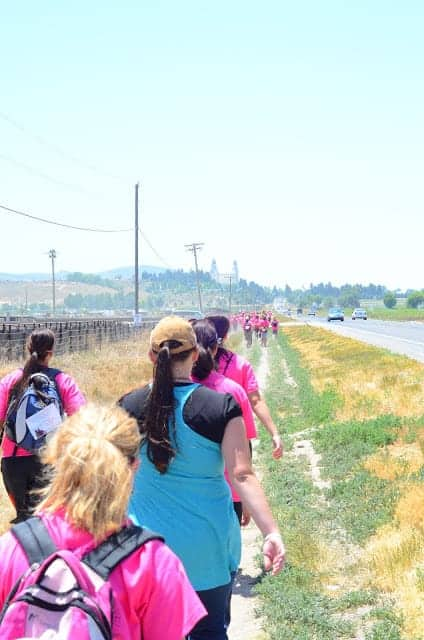A group of women and children in pink shirts walking along a path between a road and a prairie field