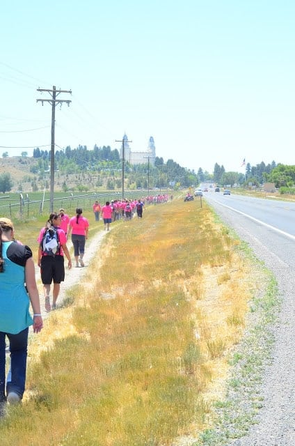A group of people wearing pink shirts walking on a path along a rural road