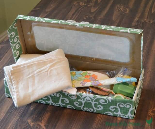 A box covered with green and white print filled with contents of a tea set, cloth napkins, and cookies