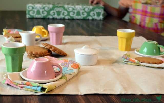 A colorful tea set on a table with floral cloth napkins and cookies