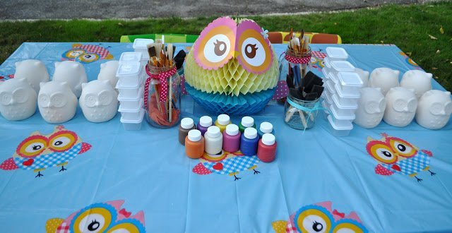 A table with painting supplies and ceramic owls for painting
