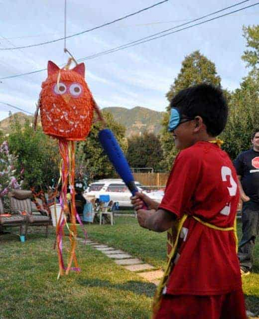 A child striking an owl pinata with a bat