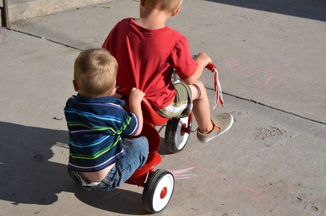 Two boys riding on a tricycle together