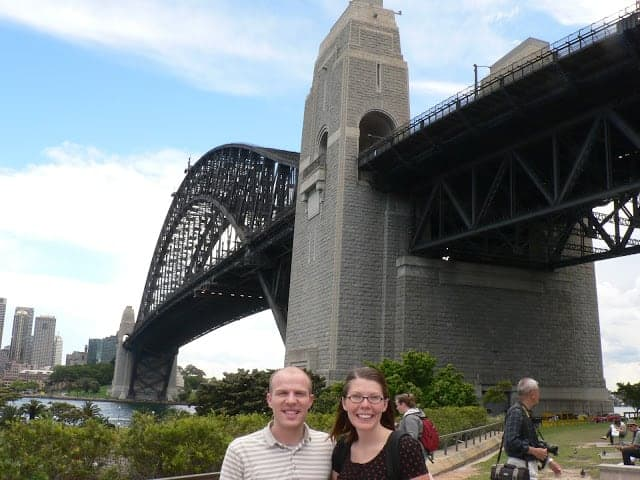A couple posing in front of a large bridge in a city