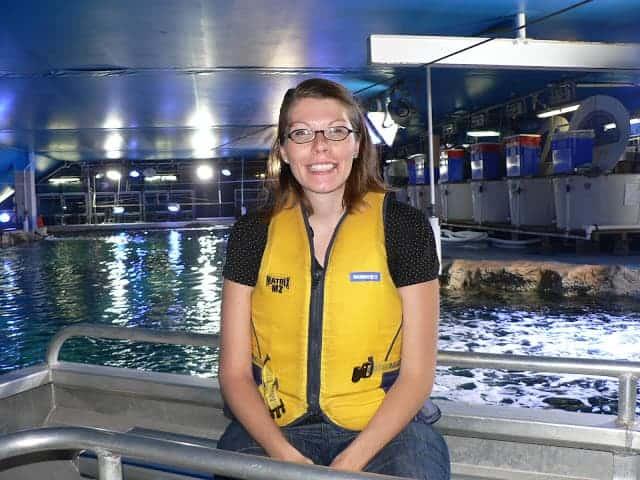 A woman sitting in a boat in a shark tank at an aquarium