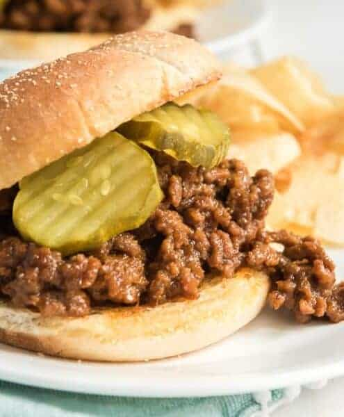 Sloppy joe on a plate with pickles and chips