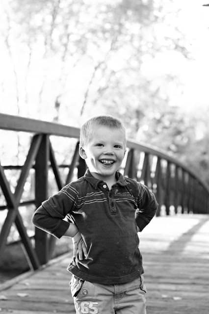 A black and white image of a little boy standing on a bridge and smiling