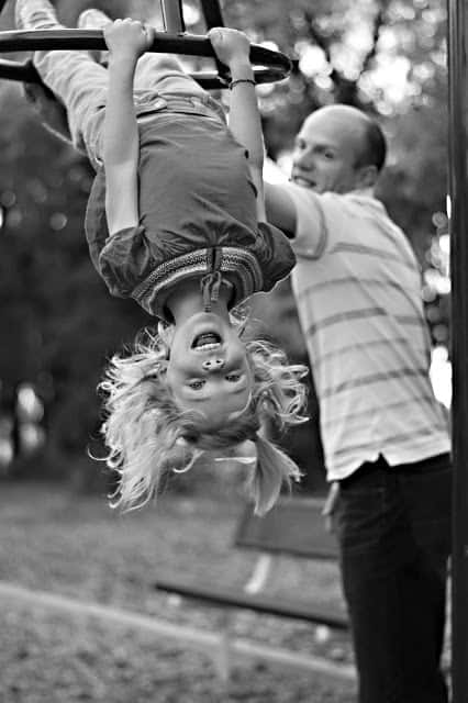 Black and white image of a dad assisting a young girl hanging upside down on a play structure