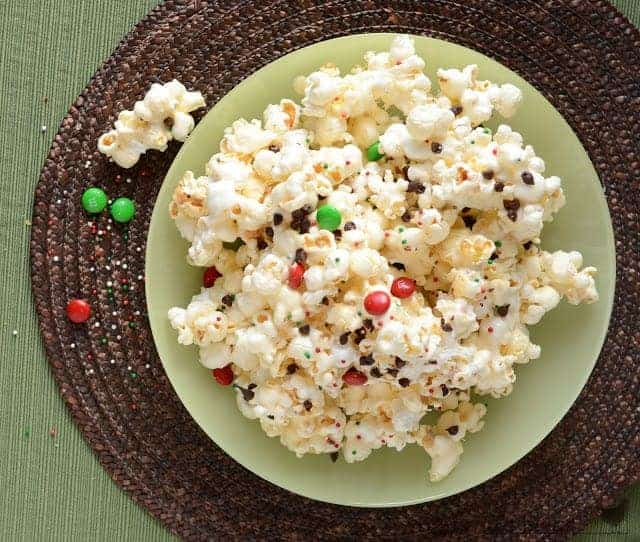 popcorn in a large green bowl on a brown placemat