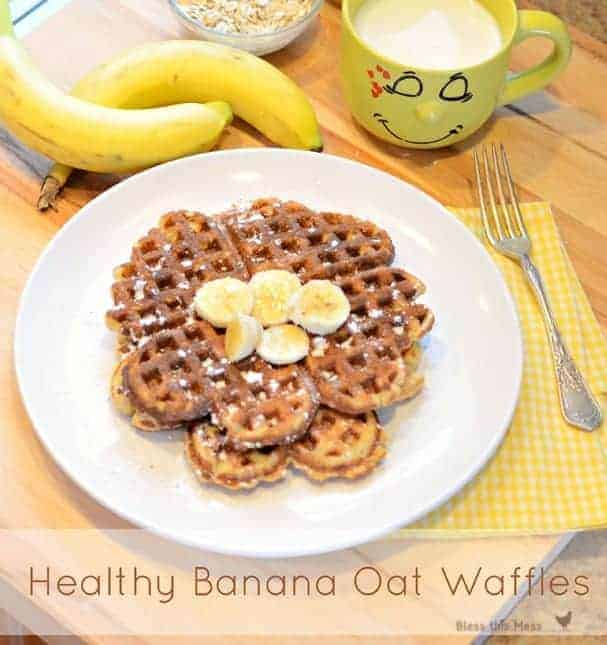 A white plate with waffles topped with bananas. A banana and a yellow cup of milk sit next to the plate.